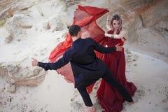 Förälskelse och passion, begrepp Härlig barnpardans i öken Mannen i svart och kvinna i rött royaltyfria bilder