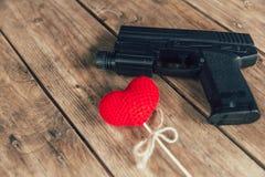 Förälskelse- och våldbegrepp: röd hjärta för för pistolvapen och förälskelse på trä Arkivbilder