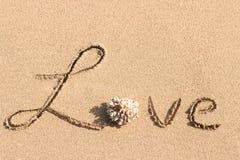 Förälskelse som är handskriven på den tropiska stranden Royaltyfri Fotografi