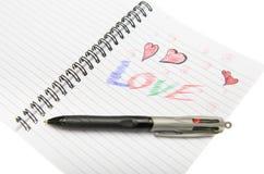 Förälskelse som är skriftlig i anteckningsbok med en penna. Arkivfoton