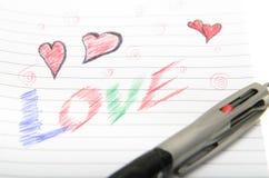 Förälskelse som är skriftlig i anteckningsbok med en penna. Royaltyfri Bild