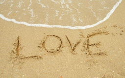 Förälskelse som är skriftlig i sand Arkivfoton