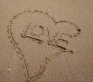 förälskelse som är skriftlig på stranden Arkivbild