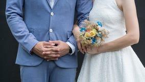 Förälskelse som gifta sig par som gifta sig buketten i händer av bruden och brudgummen Royaltyfri Foto