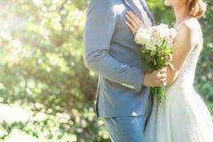 Förälskelse som gifta sig par som gifta sig buketten i händer av bruden och brudgummen Fotografering för Bildbyråer