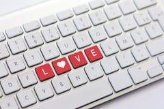 FÖRÄLSKELSE som skriver på det vita tangentbordet med en hjärta, skissar Arkivbild