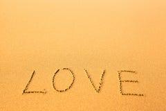 Förälskelse - text som är skriftlig vid handen i sand på en strand, hav Arkivbilder