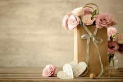 Förälskelsebakgrund med blommor och pilbågen Royaltyfri Fotografi