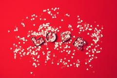 Förälskelsebegrepp med bokstäver FÖRÄLSKELSE och älsklingar på en röd backgrou Arkivbilder