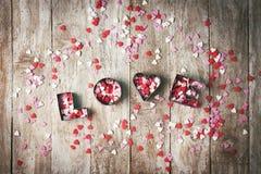 Förälskelsebegrepp med bokstäver FÖRÄLSKELSE och älsklingar på gammal träbac Royaltyfri Bild