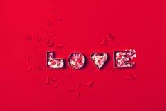 Förälskelsebegrepp med bokstäver FÖRÄLSKELSE och hjärtor på en röd bakgrund T Royaltyfria Foton