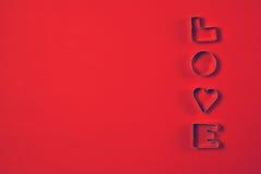 Förälskelsebegrepp med bokstavsFÖRÄLSKELSE på en röd bakgrund Intelligens för bästa sikt Royaltyfri Bild