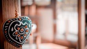 Förälskelsebegrepp med dekorativt hänga för hjärta och unfocused husbakgrund royaltyfria foton