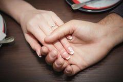 förälskelsebegrepp - som är nära av förlovade parinnehavhänder med diamantcirkeln över ferier, tänder upp bakgrund Arkivfoton