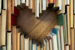 Förälskelsebegreppet av hjärtaform från gammal tappning bokar på träflo arkivfoton