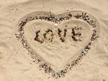 FÖRÄLSKELSEbokstäver som göras med stenar på en strand Royaltyfri Foto