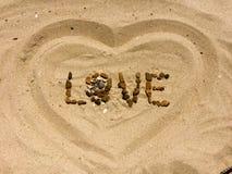 FÖRÄLSKELSEbokstäver som göras med stenar på en strand Royaltyfri Fotografi