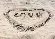FÖRÄLSKELSEbokstäver som göras med stenar på en strand Arkivbilder