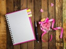 Förälskelsedagbok - tom spiralanteckningsbok och penna på trä royaltyfria bilder