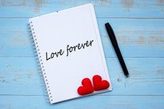 FÖRÄLSKELSEFÖR EVIGTord på anteckningsboken och penna med för hjärtaform för par röd garnering på blå trätabellbakgrund Bröllop r royaltyfri foto