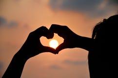 Förälskelseform vid handen med solnedgångsilhuette Royaltyfria Foton