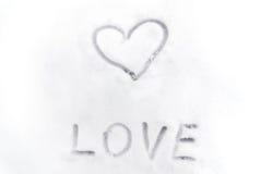 Förälskelsehjärtatecken som är skriftligt på snön Arkivbild