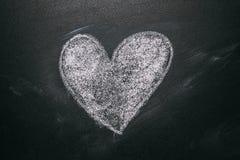 Förälskelsehjärtateckning på en svart tavla för skola Handskrivet meddelande på en svart tavlateckning för skola med en illustrer Royaltyfria Bilder