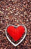 Förälskelsekaffe på valentin dag. Grillade kaffebönor med rött honom Arkivbilder