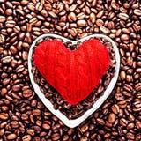 Förälskelsekaffe på valentin dag. Grillade kaffebönor med rött honom Arkivfoton