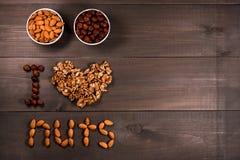 Förälskelsemuttrar för inskrift I, från muttrar, valnötter, mandlar och hasselnötter och två vita koppar med muttrar Fritt avstån Royaltyfri Foto