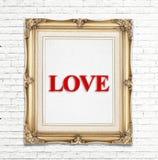 Förälskelseord i den guld- tappningfotoramen på den vita tegelstenväggen, förälskelsebegrepp Arkivbild