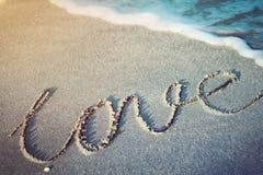 Förälskelseord som är skriftligt på en tropisk strand Arkivbilder