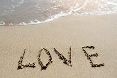 Förälskelseord som är skriftligt på sandstranden Fotografering för Bildbyråer