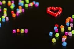 Förälskelseord vikt med färgrika kuber med bokstäver och en hjärta på en svart bakgrund arkivbild