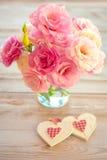 Förälskelsetappningbakgrund - härliga blommor och två handgjorda Hea Royaltyfri Foto