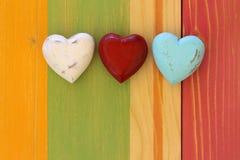 Förälskelsevalentin hjärtor på det trätextur målade brädet Backgrou Arkivfoto