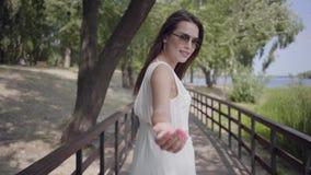 För älskvärd bärande solglasögon brunettung flicka för stående och lång vit sommarmodeklänning som promenerar en träbro lager videofilmer