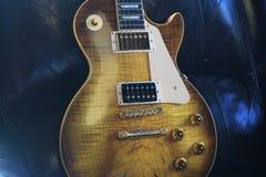 För älskvärd iconic elektrisk gitarr dam` för ` i brun läderklubbastol arkivfoton
