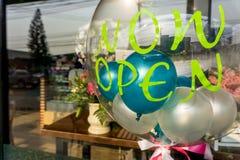 För ` öppen `-klistermärke nu på den genomskinliga ballongen med andra små färgglade ballonger inom royaltyfri foto