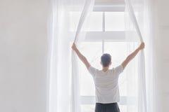 För öppningsfönster för ung man gardiner Royaltyfria Foton