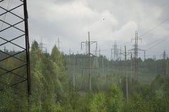 För överföringstorn för hög spänning elektriska pyloner och kraftledningar för elektricitet på grönt fält Arkivfoto