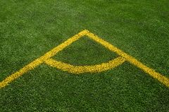 För överkant en vinkelsikt ner av den gula linjen på ett grönt fotbollfält arkivbild
