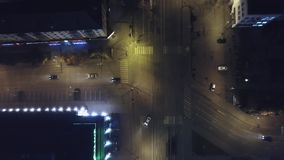 För överkant flyg- surrsikt ner av en väg på natten med bilkörning, gem Trafik på huvudvägen in mot modern stad billyktor stock video