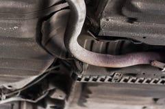 För övre rostigt järn röravgasrör för slut under bilen med elevatorbakgrund royaltyfri foto