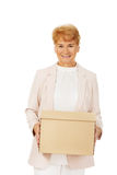 För affärskvinna för leende äldre hållande kartong Arkivfoto