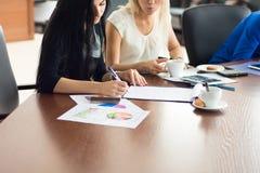 För affärskvinna för två barn tecken ett avtal i kontoret Arkivfoton