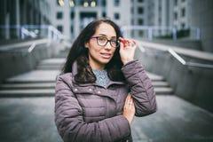 För affärskvinna för stående står den härliga unga brunetten i omslag och tröja på bakgrundskontorsbyggnad, affärsmitt i gl royaltyfri fotografi