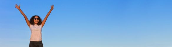 För afrikansk amerikanflicka för blandat lopp som tonåring firar blå himmel royaltyfri bild