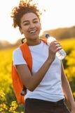 För afrikansk amerikanflicka för blandat lopp som tonåring fotvandrar dricksvatten Royaltyfri Bild