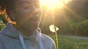 För afrikansk amerikanflicka för blandat lopp som kvinna för flicka för tonåring ung blåser maskrosen på solnedgången stock video